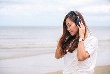 A Sad Woman Listening To Music With Headphone By The Sea