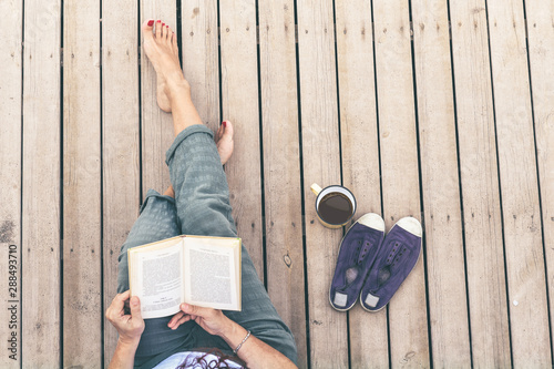 Top view of a woman reading a book, barefoot, sitting on a wooden floor Wallpaper Mural