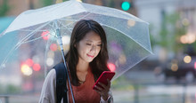 Woman Use Of Smart Phone And Hold With Umbrella In The Evening