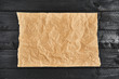 canvas print picture - Crumpled piece of parchment or baking paper on black wooden table. Top view. Copy space for text and design element.