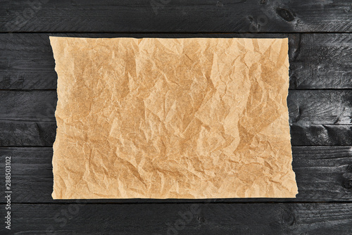 Valokuva  Crumpled piece of parchment or baking paper on black wooden table