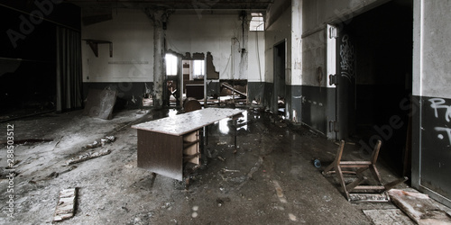 Fotografia  Ruined office with a destroyed desk, a turned-over chair, and a dirt-covered flo
