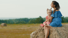 Side View Of Mother With Cute Little Daughter Sitting On A Haystack In The Meadow. Happy Family Embraces On Haystack In Summer Field. Family Concept.