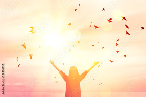 Fotografía  Copy space of woman raise hand up on sunset sky at beach and island background
