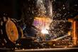 Leinwandbild Motiv Welder is welding metal part in industrial workshop.