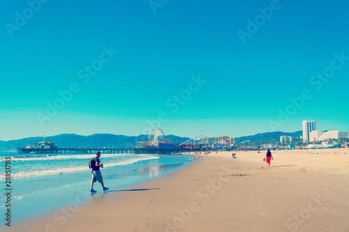 Photographer walking in world famous Santa Monica beach