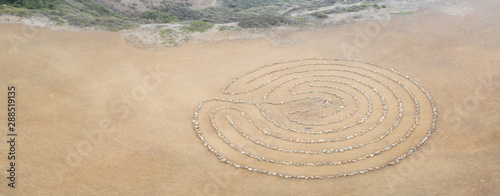 Fotobehang Stenen in het Zand A circular rock labyrinth is found on the edge of the Pacific Ocean just north of San Francisco, California. Labyrinths symbolize the journey through life from birth to spiritual awakening to death.