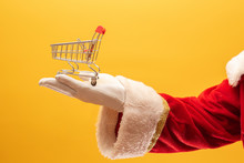 Santa Claus And The Supermarket, He Is Showing A Mini Cart. Christmas And Shopping Concept.