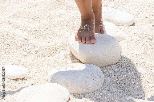 Obraz na plátně  A closeup view on the bare feet of a young child playing and standing on white stones on a sandy beach during summer vacation, stepping stones with room for copy