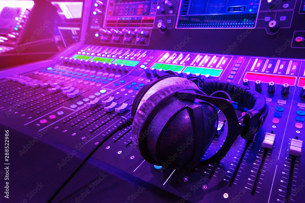 Fototapety, obrazy: Professional audio studio sound mixer console board panel with recording , faders and adjusting knobs,TV equipment.  Blue and red tone and close-up image with flare light effect.