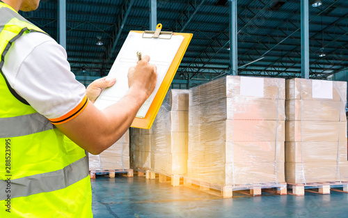 Obraz warehouse inventory management, cargo courier shipment delivery, worker hand holding clipboard inspecting checklist details of goods pallets, business industrial transportation. - fototapety do salonu
