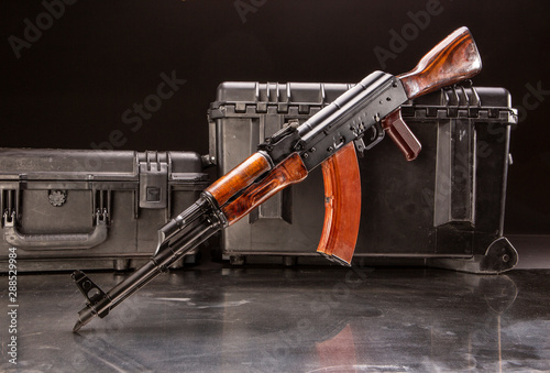 Studio shot of a Russian AK-47 in front of pelican cases, ready for travel Wallpaper Mural