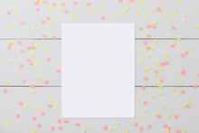 Mock-up Of Blank White Card On Light Wooden Background With Confetti, Funny Desktop For Any Holiday