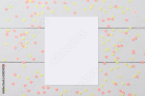 Mock-up of blank white card on light wooden background with confetti, funny desktop for any holiday © maddyz