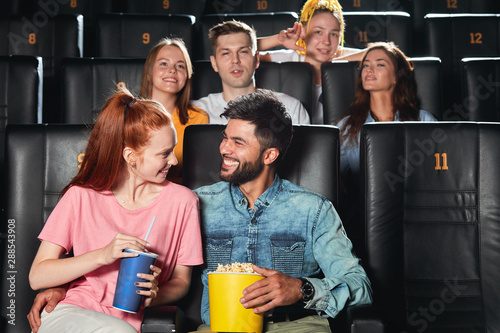 positive awesome man telling jokes to his girlfriend, entertaining her at the cinema Canvas Print