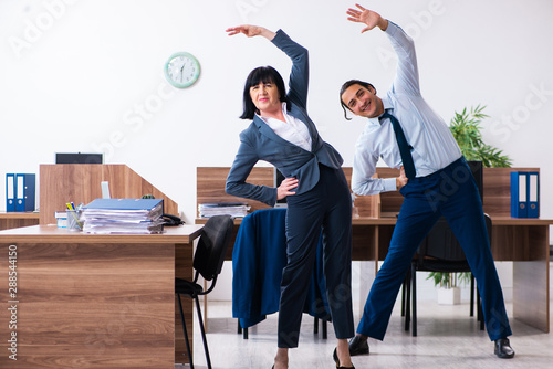 Obraz Two employees doing sport exercises in the office - fototapety do salonu