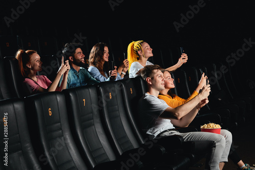 Fototapeta cheerful positive young people pirating movie with smartphones