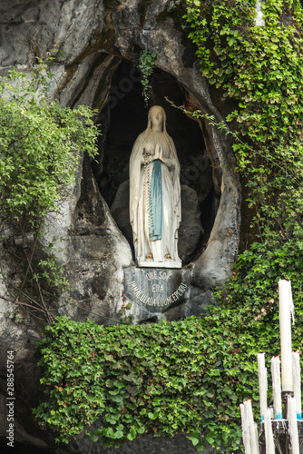 Платно Statue of Our Lady of Immaculate Conception with a rosary in the Grotto of Massa