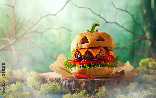 Photo Stands Snack Halloween party burger in shape of scary pumpkin on natural wooden board. Halloween food concept.