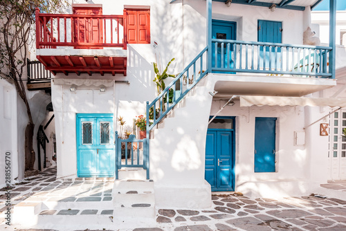 Typical Greek architecture in the white, cobbled alleys of Mykonos town, houses in the old town of Chora with colorful balconies and white churches, Cyclades, Greece