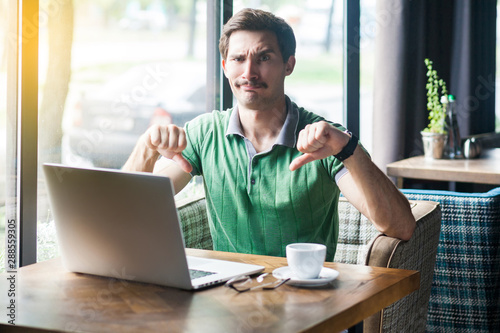 Obraz na plátně Dislike! Young dissatisfied businessman in green t-shirt sitting, working on laptop, looking at camera and showing thumbs down