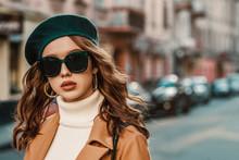 Outdoor Autumn Portrait Of Young Elegant Fashionable Lady Wearing Trendy Big Sunglasses, Green Beret, Hoop Earrings, Camel Coat, White Turtleneck,walking In Street Of European City. Copy, Empty Space