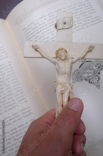 The hand holds the Cross with the crucified Jesus Christ against the background of the Bible.