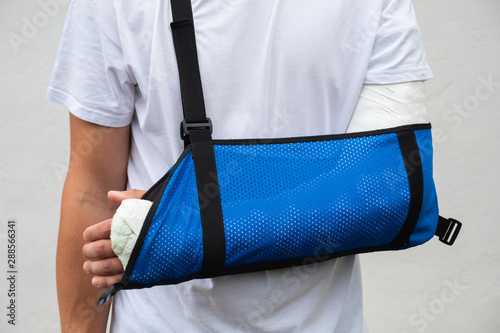 Man with broken arm wrapped medical cast plaster and blue bandage Fototapeta