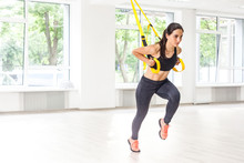 Portrait Of Young Fit Woman In Black Sportswear Training Arms With Trx Fitness Straps In The Gym Doing Push Ups Train Upper Body Chest Shoulders Pecs Triceps With Raised Leg. Indoor, Window Background