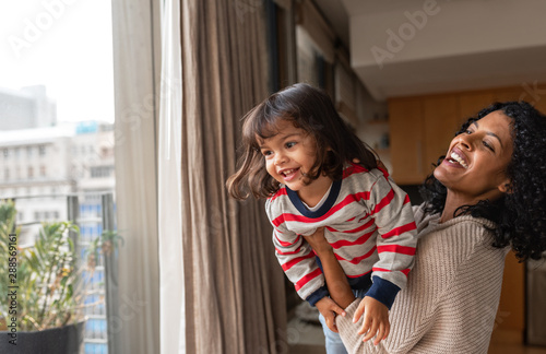 Obraz Laughing mother and small daughter playing together at home - fototapety do salonu