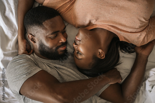 Loving African American couple looking at each other in bed Canvas Print