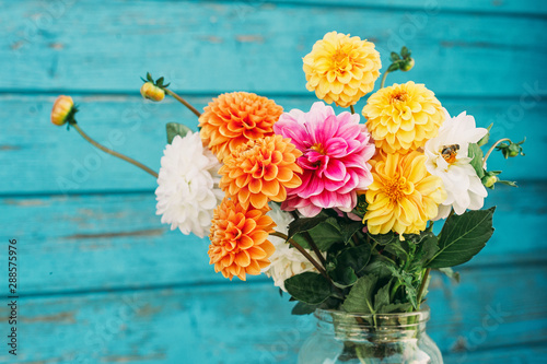 Garden Poster Dahlia Fall flowers in glass jars standing on the table outside