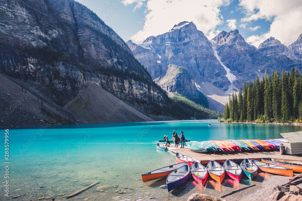 Fototapeta Colorful canoes in blue turquoise waters in Moraine Lake, Banff National Park, Alberta, Canada