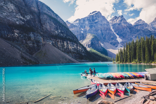 Fotografie, Tablou  Colorful canoes in blue turquoise waters in Moraine Lake, Banff National Park, A