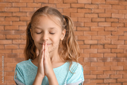 Cute little girl praying against brick wall Canvas Print