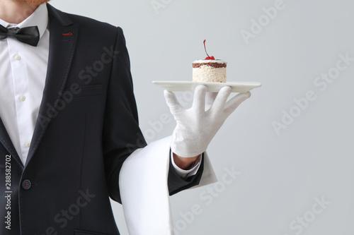 Photo Handsome waiter with dessert on light background