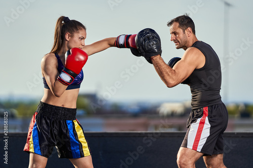 Young woman boxer hitting pads outdoor Wallpaper Mural