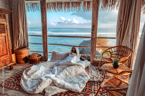 Canvas-taulu Woman enjoying morning vacations on tropical beach bungalow looking ocean view R