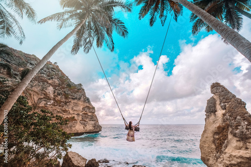 Foto auf Gartenposter Bali Beautiful girl on swing coconut palms on beach at Daimond beach, Nusa Penida island Bali ,Indonesia