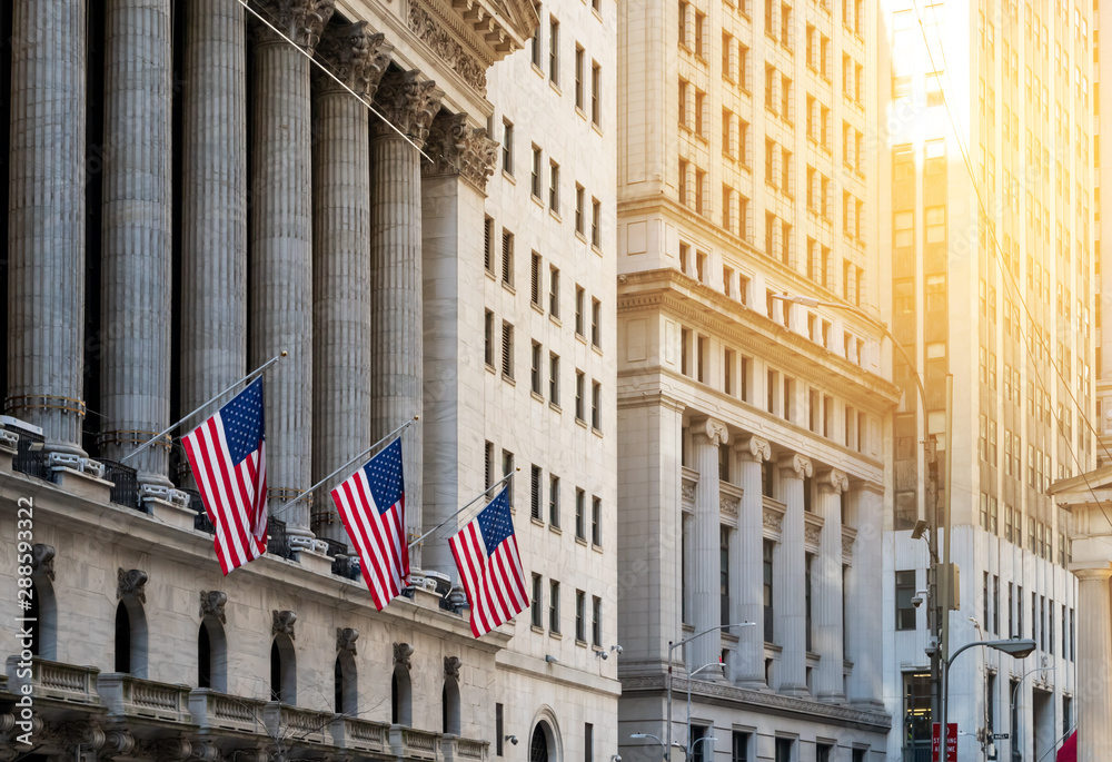 Fototapeta American flags flying in front of the historic buildings of Wall Street in the financial district of Manhattan, New York City
