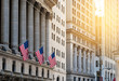 canvas print picture - American flags flying in front of the historic buildings of Wall Street in the financial district of Manhattan, New York City