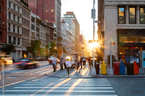 Spoed Foto op Canvas New York Man walking through the crosswalk at the busy intersection of 5th Avenue and 23rd Street in New York City with sunset background