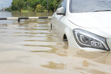 Car Driving On A Flooded Road, The Broken Car Is Parked In A Flooded Road. .