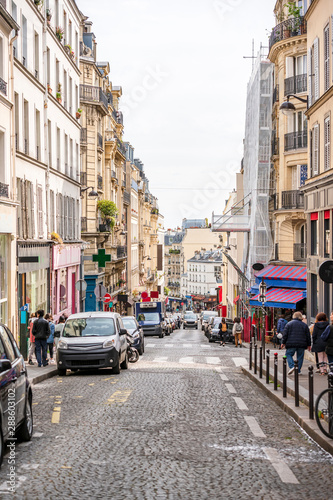 Street with shops and restaurants and residential buildings in Paris