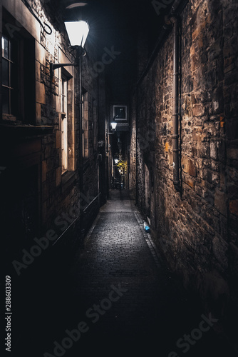 Valokuva A dark creepy narrow European alley at night, surrounded by bricks and cobblestone