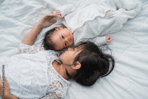 Fototapeta top view of infant baby and girl sibling enjoying together on bed obraz