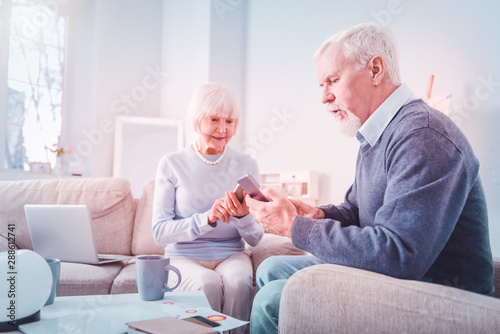 Fototapety, obrazy: Modern pensioners using their smartphones sitting on sofa at home