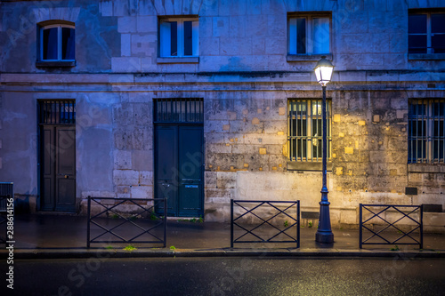 The light of lonely street lamp on the evening street of Paris after the rain