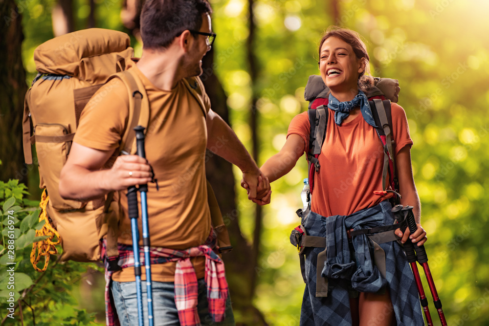 Fototapeta Cheerful couple hiking together in forest