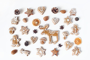 Decorative Christmas food pattern. Winter composition of gingerbread cookies, anise stars, pine cones and dry orange fruit slices isolated on white table background. Flat lay, top view.